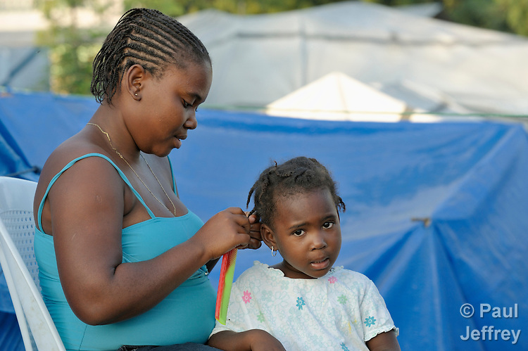 Rodelise Merville braids the hair of her daughter Gengy Badis as the girl prepares for school in a camp in Grand-Goave, Haiti, where families left homeless by the January 2010 earthquake continue to live. The ACT Alliance has supported families in this camp with a variety of services, and has rebuilt a school beside the tent city.
