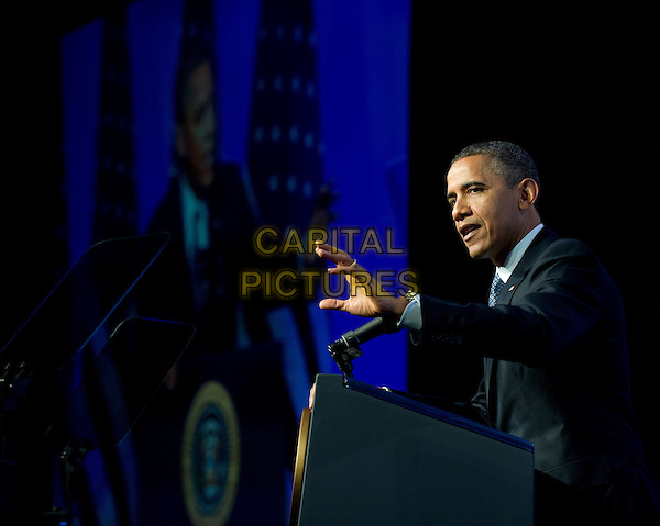 United States President Barack Obama arrives to deliver remarks at the Associated Press luncheon during the American Society of News Editors (ASNE) Convention at the Washington Marriott Wardman Park Hotel in Washington, D.C. on Tuesday, April 3, 2012.  In his remarks the President criticized the Republican budget proposals.  .half length black suit blue tie podium hand profile side.CAP/ADM/RS.©Ron Sachs / Pool via CNP/AdMedia/Capital Pictures.