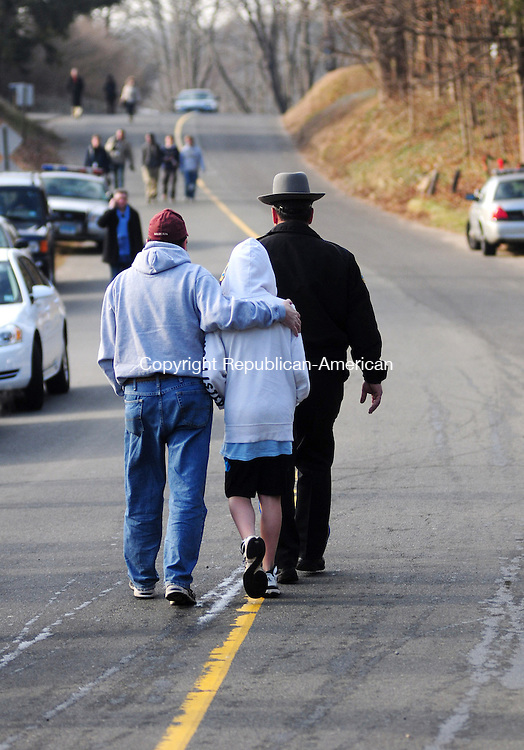 NEWTOWN, CT, 15 DEC 12-121512AJ01-A man and boy are escorted away from a pack of reporters camped out by a makeshift memorial to the victims of Friday's massacre at Sanday Hook Elementary School set up beneath the school sign. In silence the man, and boy whose hood mostly shielded his face solemnly stopped by the sign Saturday morning and laid flowers at its base before the trooper escorted them away.  Alec Johnson/ Republican-American