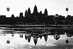 Performers run past a pond at Angkor Wat in Cambodia