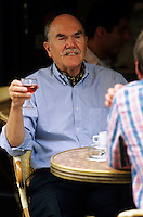 French man enjoying a glass of rose wine while talking to a friend at a pavement cafe?. France..