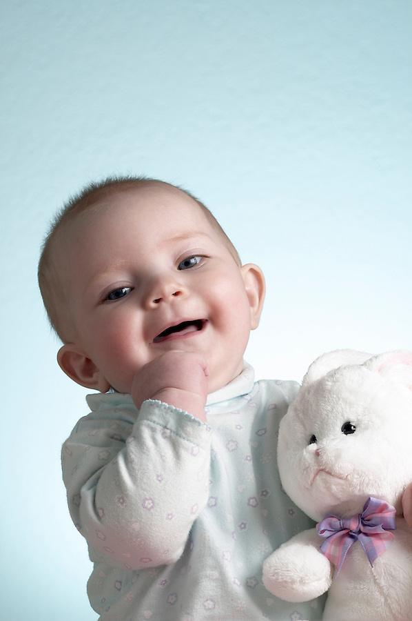 Portrait of 6 month old baby girl sitting with white stuffed rabbit