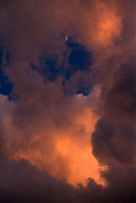 A quarter moon peers through sunset-colored thunderheads, Rocky Mtns, CO