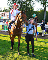 Winner of The Derek Burridge Golf & Racing Trophies Handicap Twenty Years On (red/white) ridden by Finley Marsh and trained by Richard Hughes is led into the Winners enclosure during Evening Racing at Salisbury Racecourse on 25th May 2019