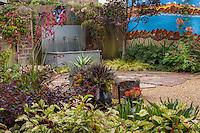 Backyard California garden patio room with painted wall, water trough fountain, patio, and colorfu foliage perennials; Schneck Garden