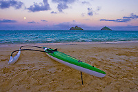 A one-man outrigger canoe drips dry following an afternoon journey. A full moon illuminates the pink sunsetting skies of windward Oahu.