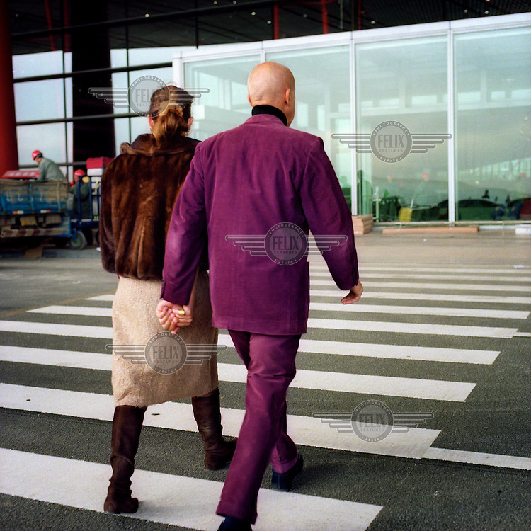Architect Norman Foster, wife his wife Elena, heads into the new Beijing Airport terminal designed by his company.