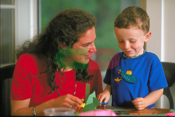 smiling woman working on crafts with young boy at table