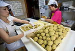 """Masako Jahana  weighs balls of dough that form the traditional """"kippan"""" confectionery, which is made from the kaabuchi citrus fruit, while Haruka Arakaki helps out at the Janaha Kippan-ten store in Naha, Okinawa, Japan on 27 June 2012. Today the Jahana family are the only people still making the traditional Kippan and Tougatsuke (which is made from """"kougan"""" winter melons) sweets that were served at the court of the Ryukyu kings over 300 years ago. Photo: Robert Gilhooly."""