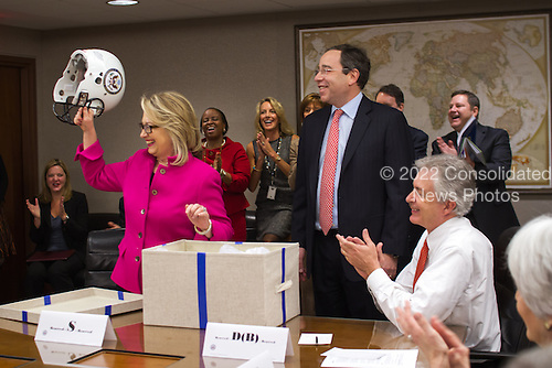 "Handout photo of United States Secretary of State Hillary Rodham Clinton's first day back at work at the State Department in Washington, D.C. following her illness on Monday, January 7, 2013.  She received gifts from her staff including a football helmet with the Department of State logo on it and a football jersey, number ""112"" referencing the record breaking number of countries she has visited as Secretary of State.  .Credit: Department of State via CNP"
