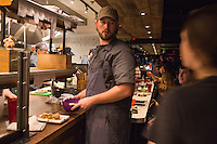 Executive Chef Hart Lowry hands off food to a waiter at the expediter station in the kitchen at Hojoko, a Japanese bar and restaurant in The Verb Hotel in the Fenway neighborhood of Boston, Massachusetts, USA, on Friday, Dec. 4, 2015. The restaurant serves food as it is ready, rather than all at once; chefs check off dishes as they are completed and handed off to waiters.
