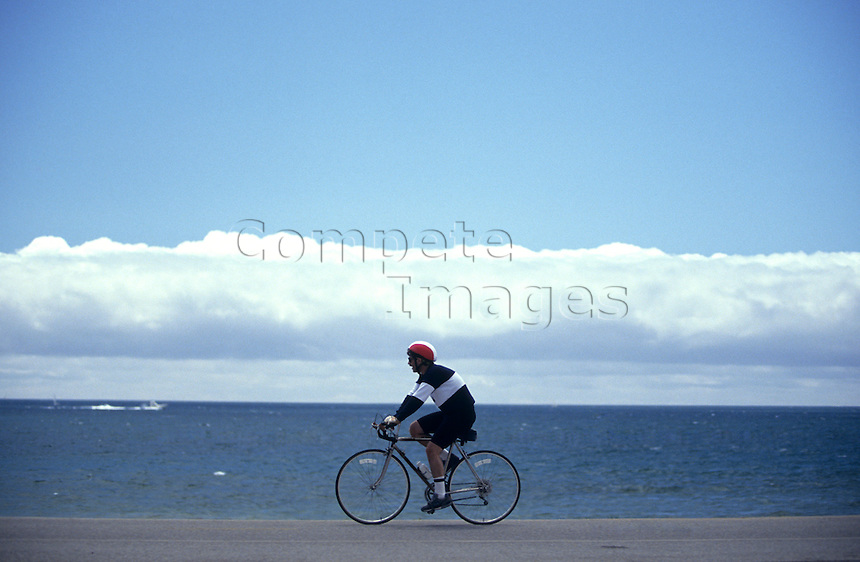 Man cycling by the waters edge of the sea
