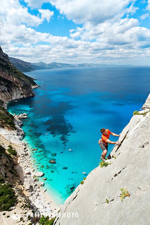 Climber above the Mediterranean on the Aguglia Tower at Cala Goloritze, Sardinia