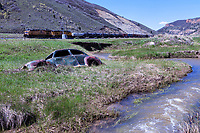 A bullet riddled classic coupe is partially submerged in the creek bed of Echo Creek in Echo Canyon as a Union Pacific freight heads eastbound.