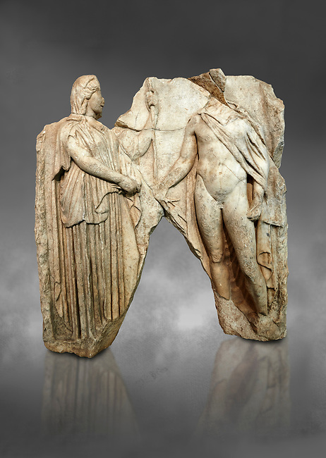 Roman Sebasteion relief  sculpture of Demeter and Triptolemos, Aphrodisias Museum, Aphrodisias, Turkey.  Against a grey background.<br /> <br /> Deneter - stately, veiled and holding a sceptre - hands a bunch of wheat stalks to the young hero Trptolomos. Demeter was the grain goddess, and it was Triptolemos, a hero from Eleusis near Athens, whom she chose to bring grain cultivation to mankind
