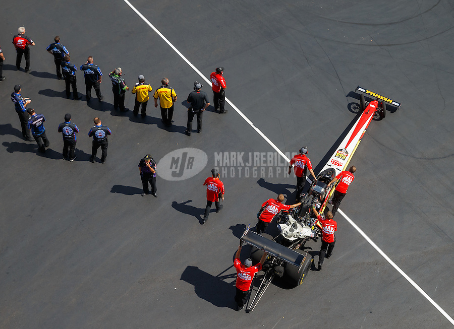 Sep 17, 2016; Concord, NC, USA; Crew members push the dragster of NHRA top fuel driver Doug Kalitta during qualifying for the Carolina Nationals at zMax Dragway. Mandatory Credit: Mark J. Rebilas-USA TODAY Sports