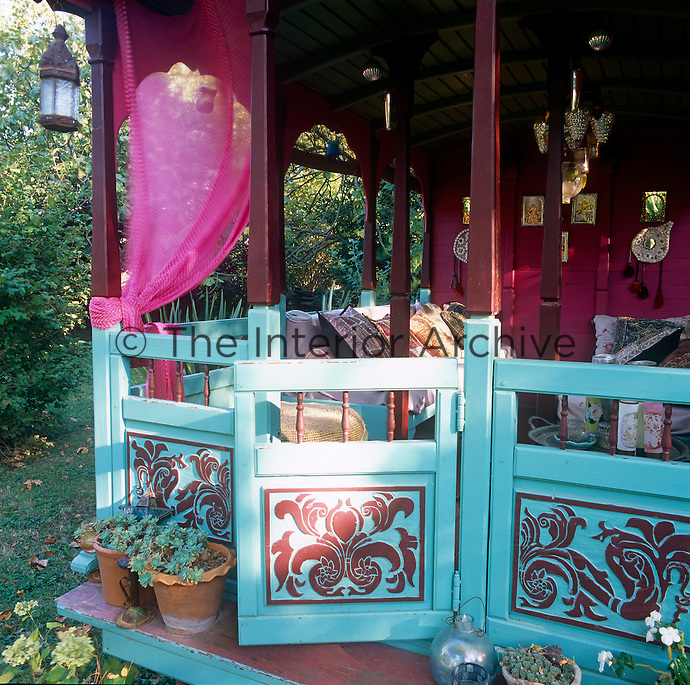 A seating area at the back of a Gypsy caravan painted in vibrant pink and blue