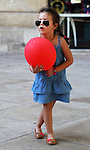 A young girl dances with her red balloon near an outdoor cafe in Bordeaux, France.