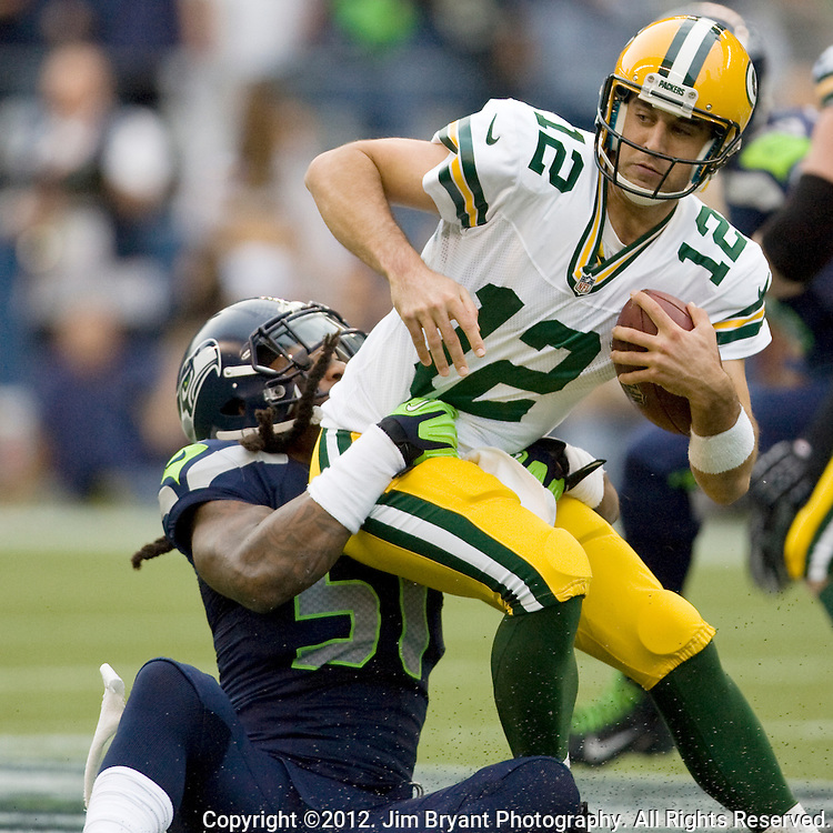 Green Bay Packers quarterback Aaron Rodgers is sacked by Seattle Seahawks Bruce Irvin at CenturyLink Field in Seattle, Washington during a Monday Night Football game,  September 24, 2012. Rodgers, who was sacked eight times -- all in the first half, completed 26 of 39 passes for 223 yards in the Packers 12-14 loss to the Seahawks.   ©2012. Jim Bryant Photo. All Rights Reserved..