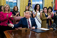 US President Donald J. Trump (C) hands out pens during a signing ceremony for the bill, 'the Women's Suffrage Centennial Commemorative Coin Act', in the Oval Office of the White House in Washington, DC, USA, 25 November 2019. Trump signed 'H.R. 2423, the Women's Suffrage Centennial Commemorative Coin Act' - a bill directing the US Treasury to mint and issue up to four hundred thousand one-dollar silver coins honoring women that played a role in gathering support for the 19th Amendment.<br /> Credit: Michael Reynolds / Pool via CNP/AdMedia