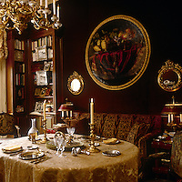 The walls of the dining room are a deep burgundy red which sets off the gilt-framed circular mirrors and the red/gold soft furnishings