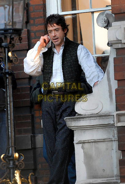 "ROBERT DOWNEY JR. .On the set of ""Sherlock Holmes"" filming around St. Paul's Cathedral in London, England, October 11th 2008..film set movie on set length white shirt belt waistcoat pinstripe grey gray trousers half 3/4 Victorian costume .CAP/IA.©Ian Allis/Capital Pictures"