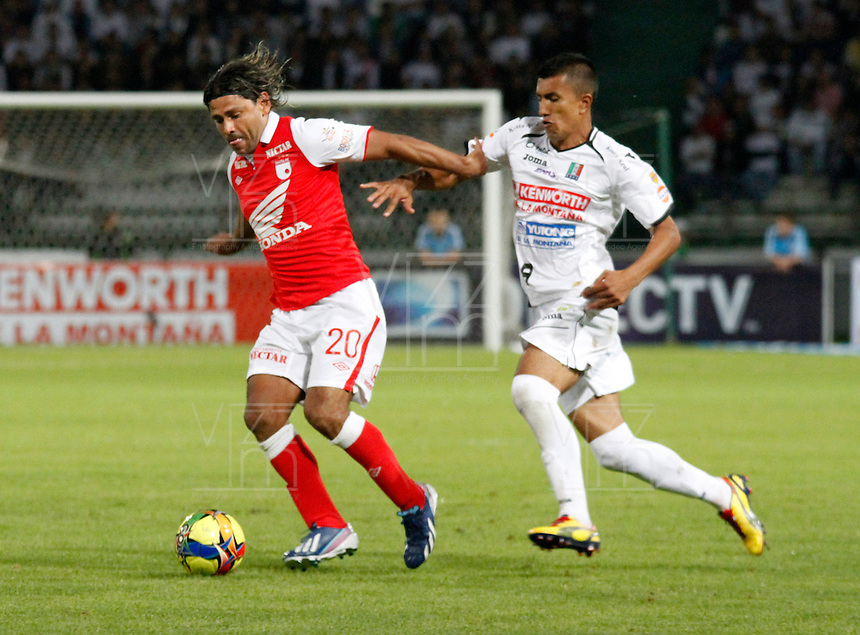 MANIZALES -COLOMBIA,05-05-2013.  Mario González del Once Caldas ataca a Gerardo Bedoya de Independiente Santa Fe, durante partido en la fecha 14 de la Liga Postobón, en el estadio Palogrande de la ciudad de Manizales, el 05 de mayo de 2013. mario Gonzalez of Once Caldas, atack to the player's Independiente Santa Fe, Gerardo Bedoya, during match on the date 14 of the League Postobón Palogrande stadium in the city of Manizales. (Photo: VizzorImage / Yonboni / Str).