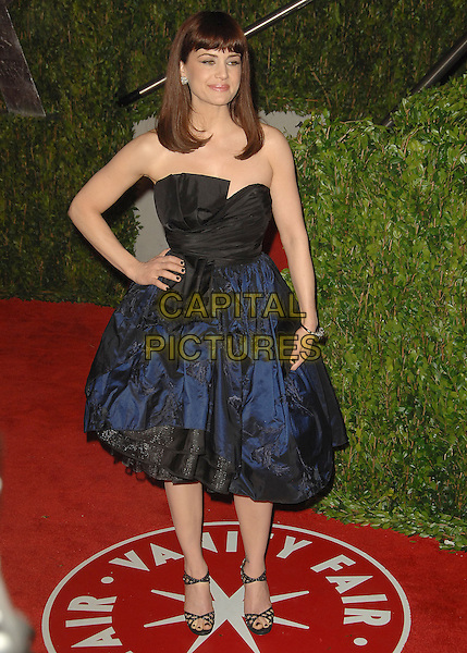 CARLA GUGINO.The 2010 Vanity Fair Oscar Party held at The Sunset Tower Hotel in West Hollywood, California, USA..March 7th, 2010.oscars full length dress black strapless blue hand on hip .CAP/RKE/DVS.©DVS/RockinExposures/Capital Pictures.