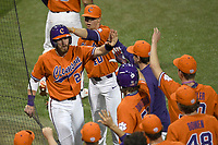 Right fielder Seth Beer (28) of the Clemson Tigers is congratulated after scoring a run in the bottom of the ninth in a game against the William and Mary Tribe on February 16, 2018, at Doug Kingsmore Stadium in Clemson, South Carolina. Clemson won, 5-4 in 10 innings. (Tom Priddy/Four Seam Images)