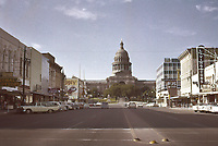 Looking up Congress Avenue to the State Capitol in downtown Austin Texas as it appeared in May 1959. Many retail shops are visible including Comal Cottons, Prices, Regal Juwelry, Rexall Drugs, Livingstons Apparel, and Continental Bus Station - Stock Image.