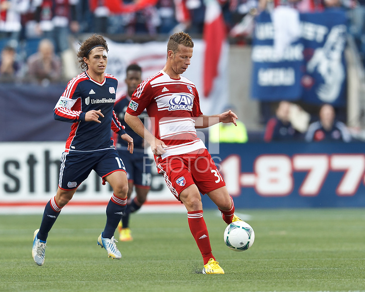 FC Dallas midfielder Michel Garbini (31) passes the ball as New England Revolution midfielder Ryan Guy (13) closes..  In a Major League Soccer (MLS) match, FC Dallas (red) defeated the New England Revolution (blue), 1-0, at Gillette Stadium on March 30, 2013.