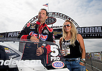 Sept. 1, 2013; Clermont, IN, USA: NHRA pro stock driver Greg Anderson (left) with wife Kim Anderson during qualifying for the US Nationals at Lucas Oil Raceway. Mandatory Credit: Mark J. Rebilas-