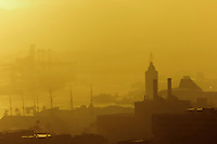 An unusually foggy golden sunset over Honolulu Harbor on O'ahu with the tallest building being the famous Aloha Tower. Built in 1926, it was the tallest building in Hawai'i and the guiding beacon for welcoming vessels.