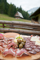 Trenta Valley, Julian Alps, Slovenia, July 2011. A farmers' breakfast of salami, cheese, and olives.  Kekceva domacija (Kekec home) lies on a clearing with spectacular views on surrounding mountains just a glimpse away from Soca River source. Slovenia boasts a very spectacular carstic landscape with high limestone rock formations oozing with waterfalls, and fast flowing cristal clear waters that run through the Soca from the Triglav National Park to the Adriatic Sea. Photo by Frits Meyst/Adventure4ever.com