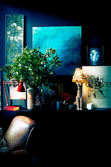 An arrangement of green foliage, a retro angle-poise lamp and other items stand on a sideboard. A collection of artworks in various shades of blue are displayed above.
