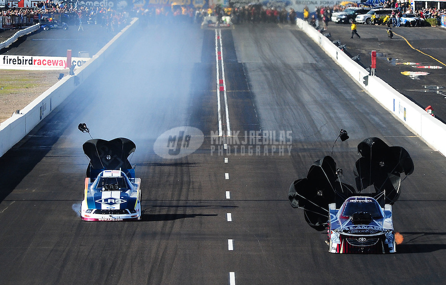 Feb. 20, 2010; Chandler, AZ, USA; NHRA funny car drivers Tim Wilkerson (left) races alongside Del Worsham during qualifying for the Arizona Nationals at Firebird International Raceway. Mandatory Credit: Mark J. Rebilas-