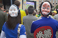 Germany, DEU, Dortmund, 2006-Jun-22: FIFA football world cup (USA: soccer world cup) 2006 in Germany; two Japanese football fans with funny masks on the back of their heads watching a world cup match in a public viewing zone.