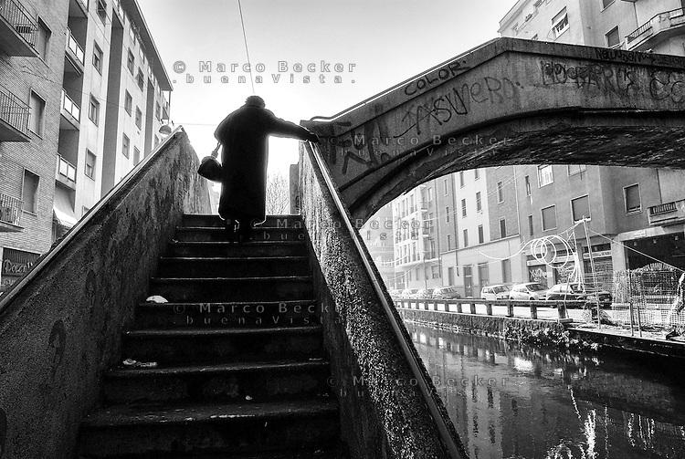 Milano, una anziana signora con borsetta sale gli scalini di uno dei ponti sul Naviglio Pavese --- Milan, an old lady with purse climbs up the stairs of one of the bridges of the Naviglio Pavese canal