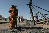 BLACK ROCK CITY,NV - AUGUST 31, 2008: Participants gather around the ashes of what was the 'Man' the night before, many collect melted scraps of the installation as a momento. The finale of the Burning Man event, August 31, 2008.