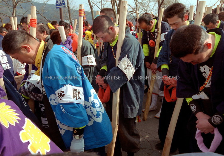 """4/2/2004--Suwa, Japan..Members of a log team bow and pray for their safety during the Onbashira Festval in Suwa, Japan...The basic purpose of the 1200 year old Onbashira Festival is rooted in Shinto, the indigenous religion of Japan. In the Shinto way of thinking, the Gods, or kami, are living in the natural environment which surrounds human beings. The Onbashira Festival serves as a reminder of the importance of nature to human beings: large fir trees (symbolic """"gods"""") are brought down from the mountains, carried into town and set to stand at the outskirts of the Suwa Grand Shrine. In this way, the people of the Suwa region never completely lose their contact with nature and the gods, and they renew this contact at least once every 6 years through Onbashira Festival..Photograph by Stuart Isett.©2004 Stuart Isett. All rights reserved"""