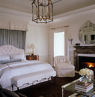 Fresh white bedlinen and painted panelling give a light and airy feel to this pretty and feminine bedroom