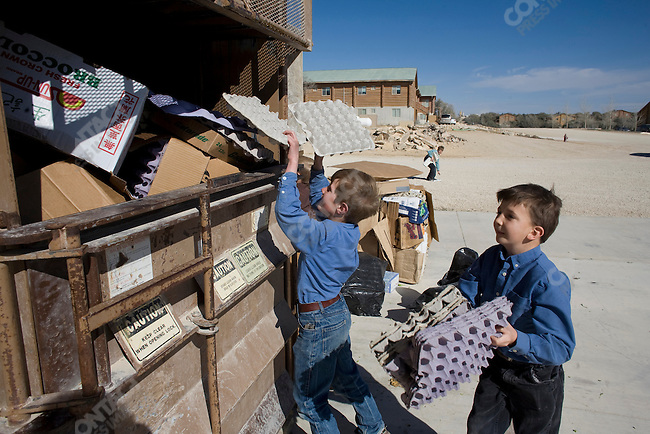 "Fundamentalist Mormon group F.L.D.S.,  boys load cardboard into the recycler at the Storehouse on the ""Yearning for Zion"" compound in Eldorado, Texas, USA, February 12, 2009"