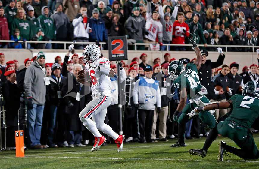Ohio State Buckeyes quarterback J.T. Barrett (16) scores a rushing touchdown against Michigan State Spartans linebacker Ed Davis (43) during the 1st quarter at Spartan Stadium in East Lansing, Michigan on November 8, 2014.  (Dispatch photo by Kyle Robertson)