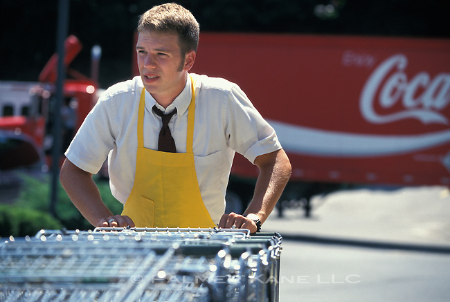 Teenage boy with after school job collects shopping carts from parking lot