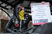 November 23, 2011, Toronto Police deployed in significant numbers this morning, beginning the process of evicting the Occupy Toronto tent camp from St. James Park.  Here, one unidentified female protest supporter holds her ground and a sign objecting to the concentration of wealth by a few.