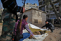 "Hisham (at right) and Free Syria Army civilian volunteers prepare a body for burial at Martyr's park (formerly known as Cobbler's Park) in the Bustan Al-Qasr neighborhood of Aleppo. ..The park, under Free Syria Army control,  has been renamed ""Martyr's Park""  since the revolution arrived in Aleppo in July of 2012.  A patch of dirt that lies next to children's swings, slides and monkey bars now serves as this neighborhood's makeshift cemetery. On January 29, 2011, 110 bodies floated down a water canal (which is part of the river Qweiq) that separates this rebel-controlled area from the regime side on the opposite side of the canal. Many of the showed signs of torture and most where executed with their hands bound behind their backs. In the weeks after this incident, dozens more bodies have been discovered in the canal - many of the victims that have not been claimed by family members have been buried here."