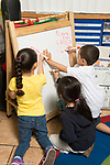 Education Preschool 4-5 year olds group of two girls and boy writing with dry erase markers on board in classroom