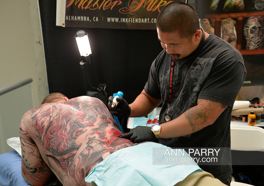 Garden City, New York, USA. September 14, 2014. Tattoo artist MASTER MIKE, from Cambodia, tattoos the back of a man lying prone at the United Ink Flight 914 tattoo convention at the Cradle of Aviation museum of Long Island.