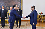 A handout picture released by the Egyptian Presidency on June 14, 2018 shows newly-appointed Prime Minister Mostafa Madbouli (L) shaking hands with President Abdel Fattah al-Sisi (R) during his swearing-in ceremony at the presidential palace in the capital Cairo. Photo by Egyptian President Office