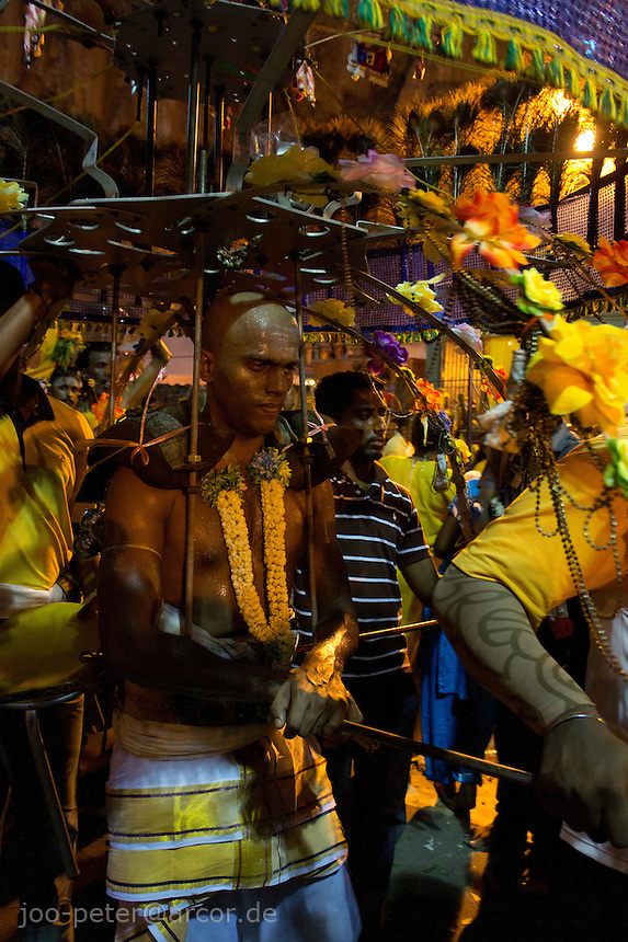 man carrying kavari  at Thaipusam ceremonies,  Batu Caves, Kuala Lumpur, Malaysia, 2012. man carrying kavari  at Thaipusam ceremonies,  Batu Caves, Kuala Lumpur, Malaysia, 2012. Thaipusam ceremonies, celebrated by tamile Hindu community in Malaysia, take place  in Sanctuary of Batu Caves at the border of Kuala Lumpur, each year around end of January or beginning of February, according to Hindu moon calendar. The event is paying hommage to Lord Murugan, a spirit or god created by Shiva to lead the army of gods against the army of evil demons, finally defeating the evil spirits. There are many ways to present offerings or sacrifices for this major religious event. Devotees mortify their bodies by carrying heavy kavaris with spears fixed in their skin or fruits, flowers and little post with holy milk fixed with hooks in their skin, ascending the stairways to the sanctuary in trance, `followed by assistant  taking care and musicians playing loud and fast rhythmic trance music.  Many families shave their head in a ritual before ascending the stairways, as part of rituals to obtain salvation for their ancestors.
